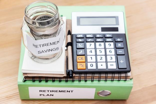 Cartella con l'etichetta piano di pensionamento e soldi in barattolo