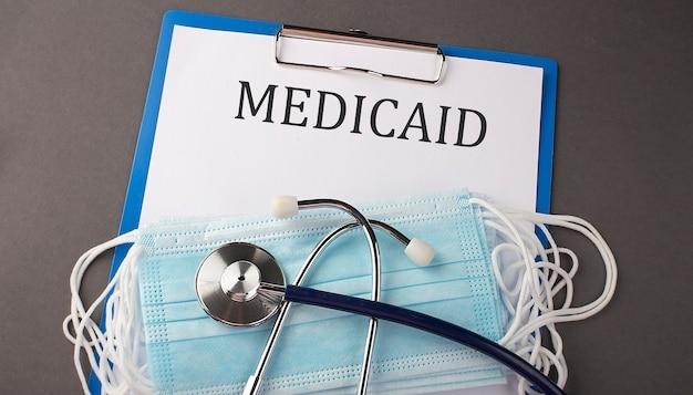 Cartella con testo cartaceo medicaid, su un tavolo con uno stetoscopio e maschere mediche