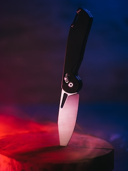Bellissimo coltello pieghevole, colori alla moda sfondo fumoso al neon