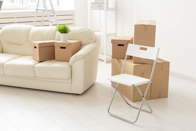 Il divano e le scatole della sedia pieghevole si trovano nel nuovo soggiorno quando i residenti si trasferiscono in un nuovo appartamento. il