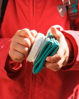 Bottiglia di silicone pieghevole in mano di bambina in giacca rossa