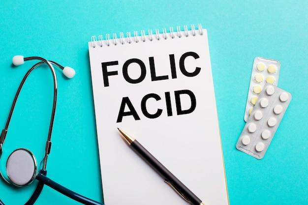 Acido folico scritto in un blocco note bianco vicino a uno stetoscopio, penne e pillole su uno sfondo azzurro. concetto medico