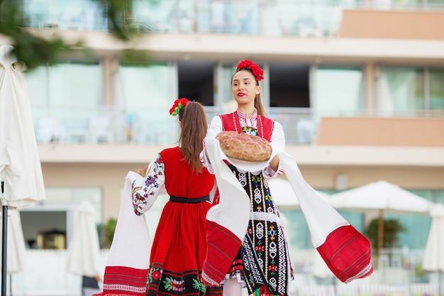 Un gruppo folcloristico vestito con abiti tradizionali sta eseguendo danze nazionali bulgare