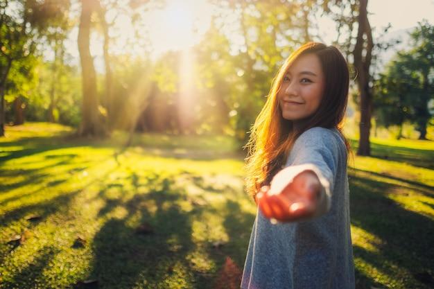 Seguimi, una bella donna asiatica che si tiene per mano e conduce nel parco prima del tramonto