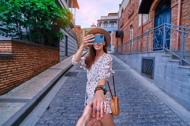 Seguimi concetto e viaggiando insieme. felice sorridente gioiosa ragazza viaggiatrice tiene la mano del ragazzo e scatta foto su una fotocamera del telefono durante il fine settimana di vacanza durante le visite turistiche