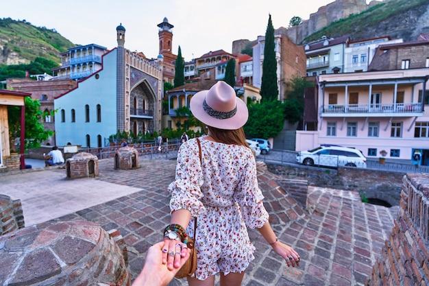 Seguimi e viaggiamo insieme. ragazza viaggiatore che indossa un cappello e una tuta corta tiene la mano dei fidanzati e conduce ai bagni di zolfo nel quartiere abanotubani della vecchia città di tbilisi, georgia