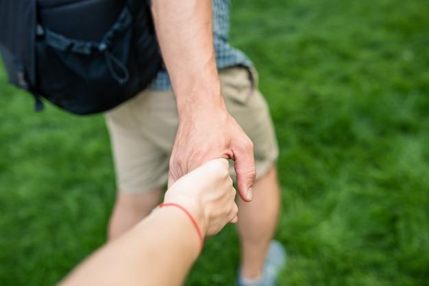 Seguimi. giovane che tiene la mano e conduce la ragazza al paesaggio naturale. vista dal lato posteriore.