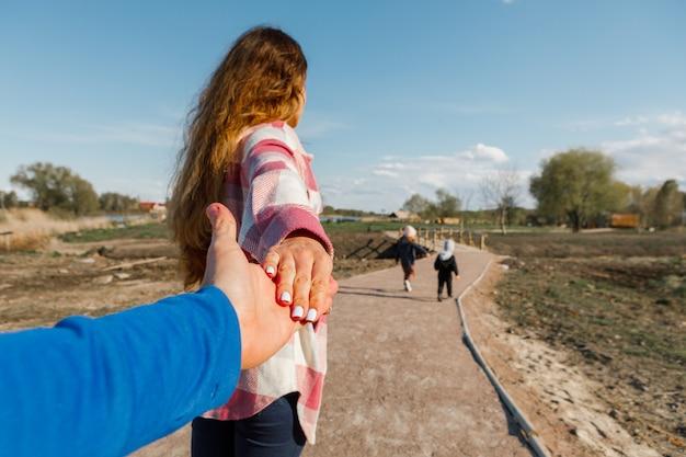 Seguimi. viaggiatore della giovane donna che tiene la mano dell'uomo. concetto di viaggio di vacanza di coppia