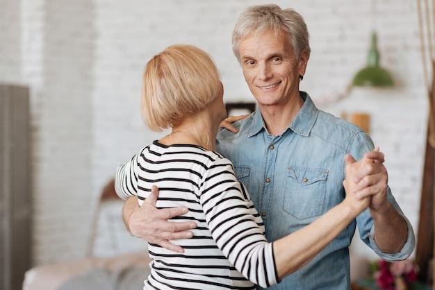 Seguendo il suo esempio. gentile signore anziano emotivo sentirsi romantico e chiedere alla sua signora di ballare mentre si godono il loro tempo libero insieme