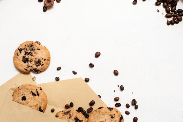 Appassionato di dolci e concetto di panetterie. piccoli regali eleganti con focaccine al cioccolato fatte in casa e decorazione di semi di caffè su sfondo bianco, vista dall'alto con spazio libero