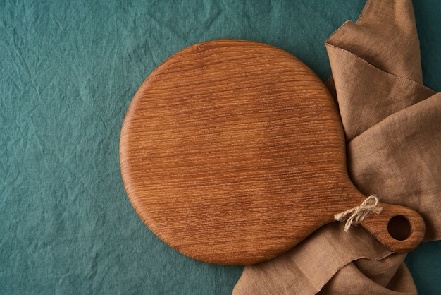 Mockup di sfondo di cibo con tagliere di legno rotondo sulla tovaglia di lino verde scuro