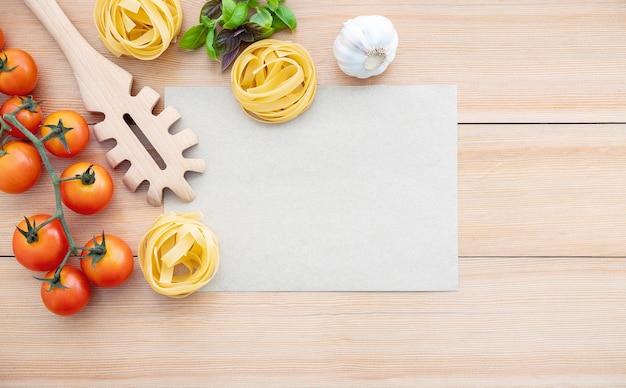 Sfondo di cibo per gustosi piatti italiani con carta marrone vuota e mestolo di pasta vintage su fondo in legno.