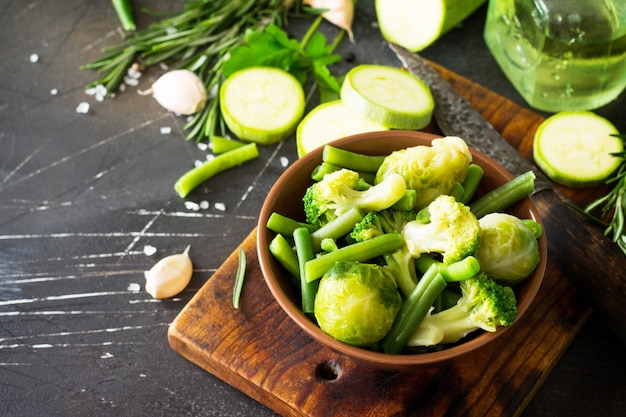 Sfondo di cibo varie verdure verdi estive spezie olio d'oliva ed erbe fresche