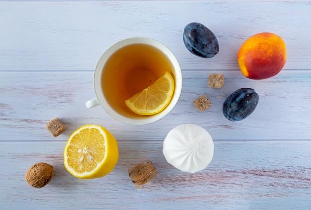 Sfondo di cibo con una tazza di tè, limone, prugne mature e nettarine, noci e marshmallow bianchi