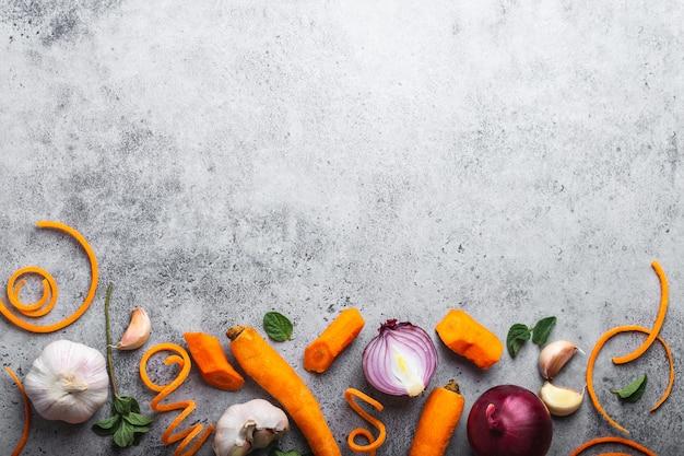 Sfondo di cibo con spazio libero per il testo. primo piano, vista dall'alto di carota cruda fresca tagliata, cipolle, aglio, erbe aromatiche su fondo rustico in pietra grigia, cucina, cibo vegetariano o concetto di alimentazione sana