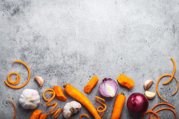 Sfondo di cibo con spazio libero per il testo. primo piano, vista dall'alto di carota cruda fresca tagliata, cipolle, aglio su fondo rustico in pietra grigia, cucina, cibo vegetariano o concetto di alimentazione sana