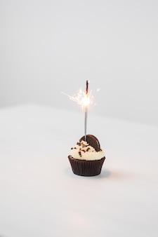 Cibo, panetteria, vacanze, buon compleanno e concetto di dessert - delizioso cupcake con sparkler e biscotto sul tavolo bianco