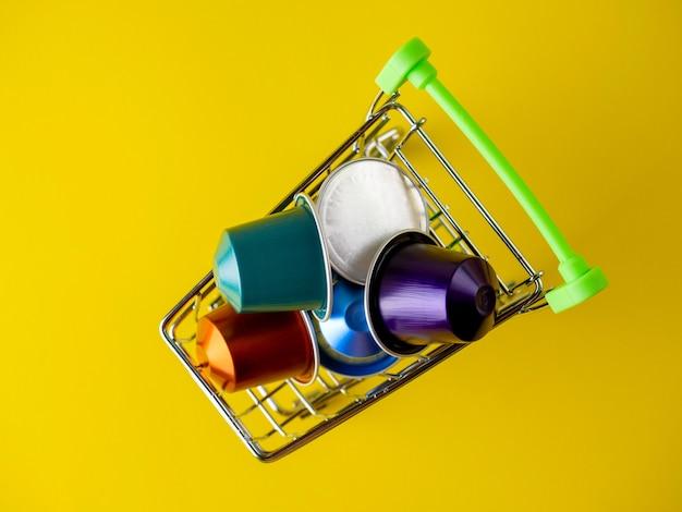 Un cesto di cibo pieno di capsule di caffè in alluminio colorato su sfondo giallo. vista dall'alto, posizione piatta
