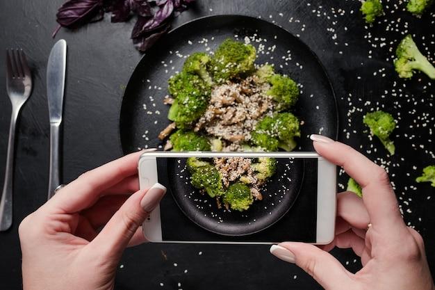 Il food blogger fa una foto mobile di insalata di verdure. attività sui social network. corretto stile di vita nutrizionale.