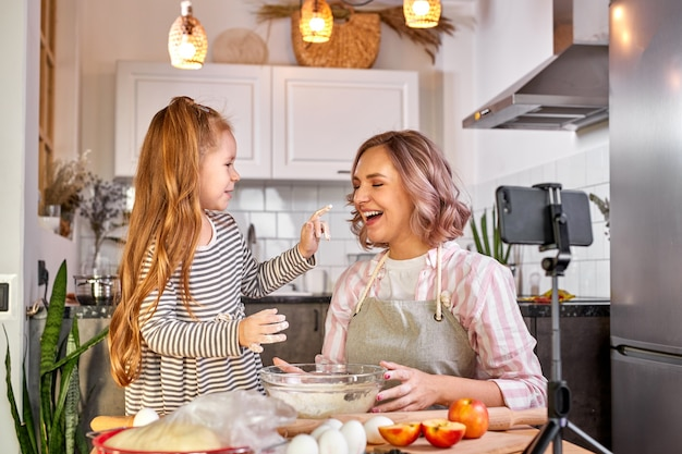 Madre e figlia di food blogger preparano l'impasto, cuociono i biscotti, registrano video sulla fotocamera, divertiti. in cucina