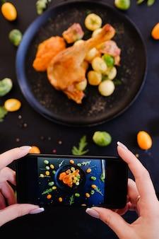 Concetto della foto dello smartphone dell'alimento del ristorante di blogger dell'alimento. dipendenza dai social network. delizioso piatto di cosce di pollo.