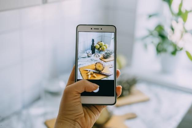 Il food blogger scatta una foto sullo smartphone per i social network mano femminile che tiene il cellulare con foto