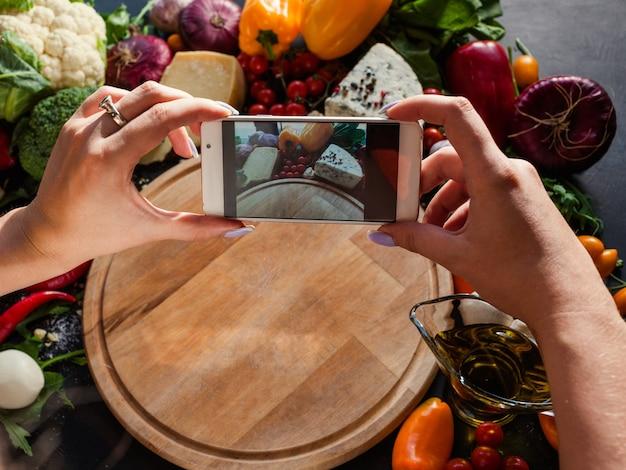 Food blogger che scatta foto sul suo smartphone. blog social network concetto di tecnologia moderna
