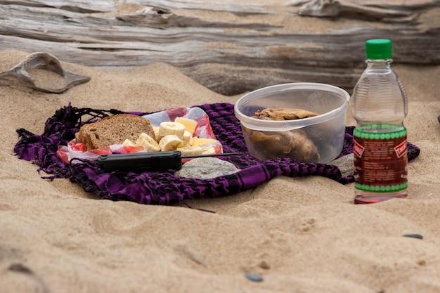 Cibo nella campagna sulla sabbia con un registro. set di cibo da picnic. banane, pane, pollo, succo di frutta, giace un coltello. il pane e la banana vengono tagliati a pezzi.