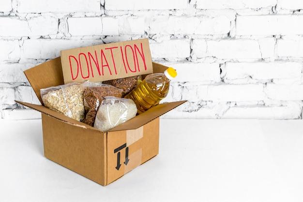 Alimento in scatola di donazione del cartone su un fondo bianco. scorte anticrisi di beni essenziali per il periodo di isolamento in quarantena. consegna del cibo, coronavirus. la carenza di cibo. copia spazio.