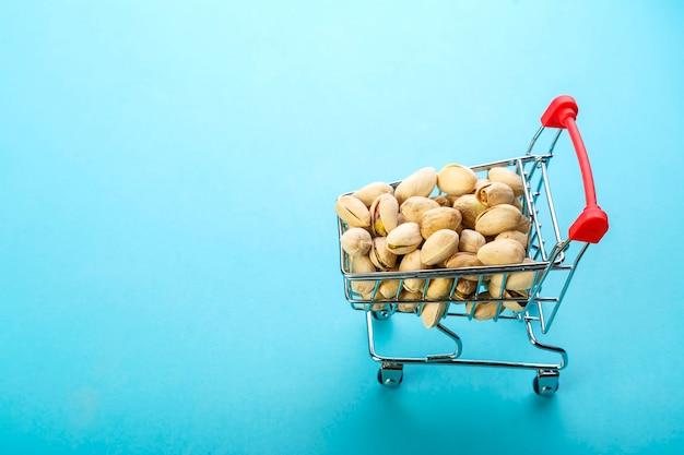 Carrello alimentare riempito con pistacchi in gusci su una parete blu. copia spazio