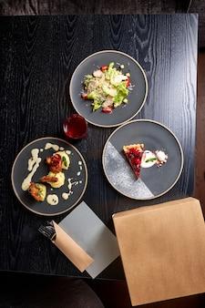 Composizione del cibo sulla tavola nel ricco ristorante esclusivo cibo sul piatto, tre diversi piatti cucinati e serviti per i clienti. vista dall'alto