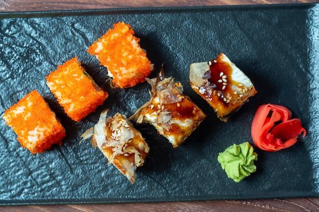 Composizione degli alimenti con involtini di sushi. una varietà di sushi su un piatto nero, accanto a zenzero sottaceto e wasabi. vista dall'alto, posizione piatta