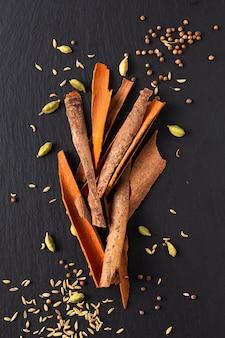 Assortimento di concetto alimentare baccelli di cardamomo spezie orientali, semi di coriandolo, finocchio e cannella cassia bark sticks su ardesia nera