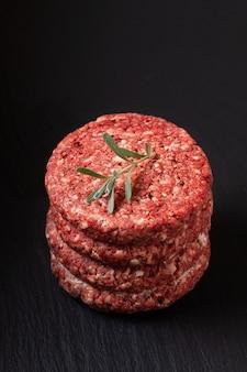 Food concept stack di tortino di manzo macinato o hamburger di manzo sul bordo di ardesia nera con spazio di copia
