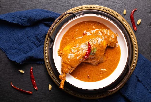 Concetto di cibo pollo tikka masala fatto in casa o curry rosso su sfondo nero
