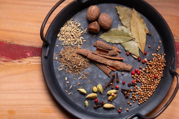 Il concetto di cibo ingredienti di spezie masala curry in vintage vassoio di ferro su legno con copia spazio