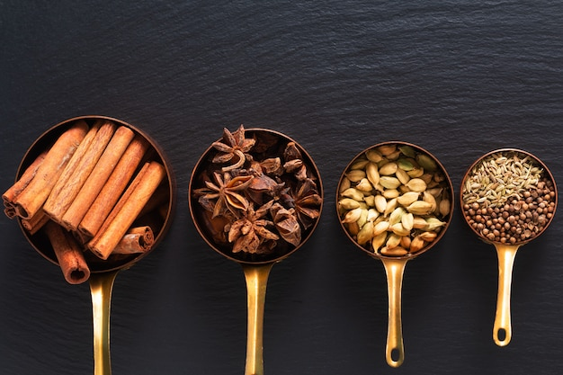 Il concetto di cibo mix di spezie masala, cannella, finocchio, anice stellato, semi di coriandolo e baccelli di cannella in tazza di rame sul pannello di ardesia nera