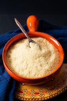 Couscous crudo organico di concetto dell'alimento in ciotola arancio