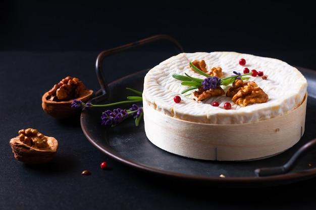 Il concetto di cibo organico morbido formaggio cremoso camembert francese su sfondo nero con copia space