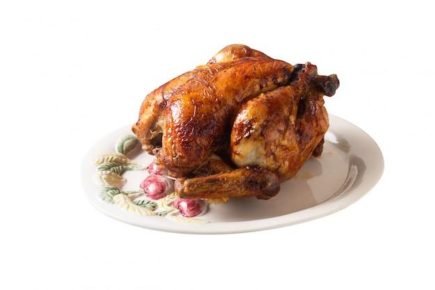 Concetto dell'alimento pollo organico intero arrostito e grigliato sul piatto ceramico bianco isolato