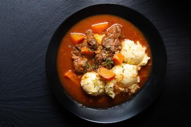 Food concept spot fosuc stufato di manzo classico fatto in casa con purè di patate nel piatto nero