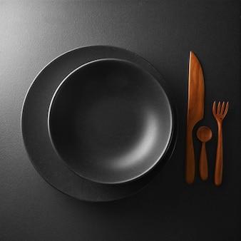 Concetto di cibo - vista dall'alto della piastra nera con coltello, cucchiaio e coltello sul tavolo scuro