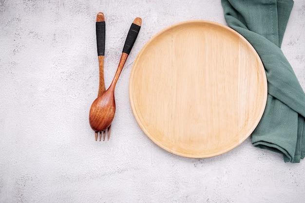 Immagine concettuale di cibo del piatto di legno con cucchiaio e forchetta su cemento bianco.