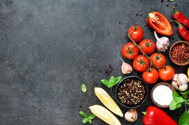 Sfondo di cucina cibo sulla tavola nera. verdure fresche, spezie, erbe aromatiche. ingredienti per cucinare con spazio per il testo.