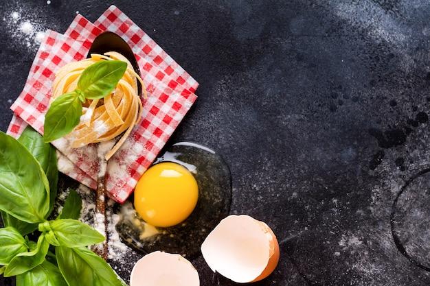 Priorità bassa di concetto di cottura del cibo. ingredienti per la tradizionale pasta fatta in casa italiana pomodori, uova crude, foglie di basilico sul tavolo di fondo in cemento scuro. vista dall'alto con copia spazio