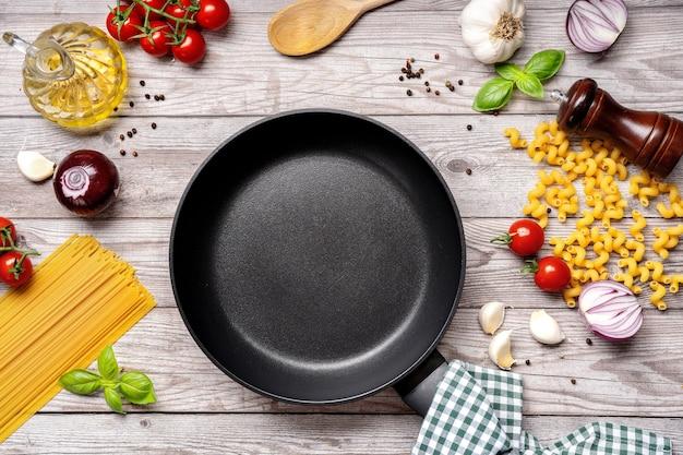 Tavolo da cucina con padella vuota, pasta e verdure sulla tavola di legno grigio. modello. copia spazio. vista dall'alto