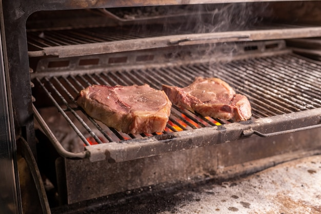 Cibo, artigianato e concetto delizioso: cucinare una bistecca alla griglia.