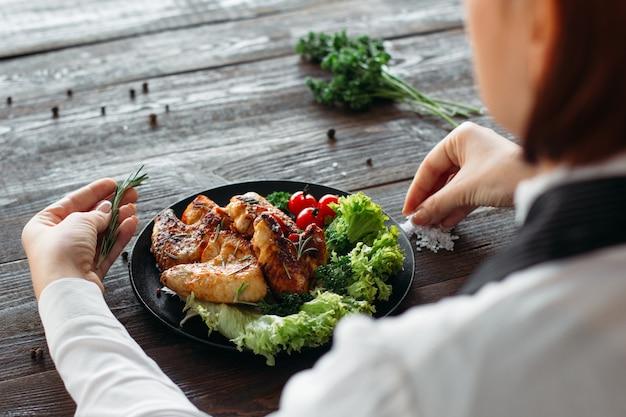 Decorazione alimentare. cameriere che serve piatto di carne con spezie ed erbe aromatiche.