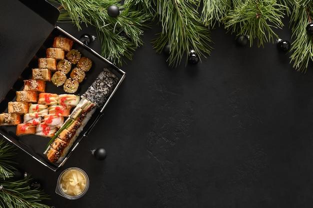 Consegna del cibo per sushi asiatico impostato per la cena di natale o la festa di capodanno su sfondo nero.