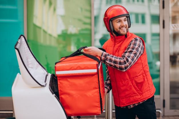 Ragazzo delle consegne di cibo che consegna cibo in scooter